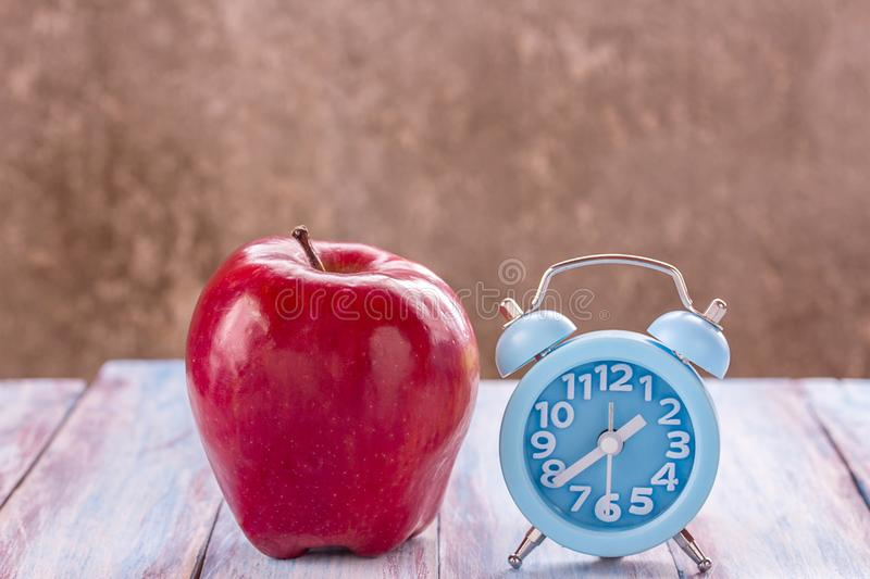 Apple and alarm clock on wood table at the morning. stock photos