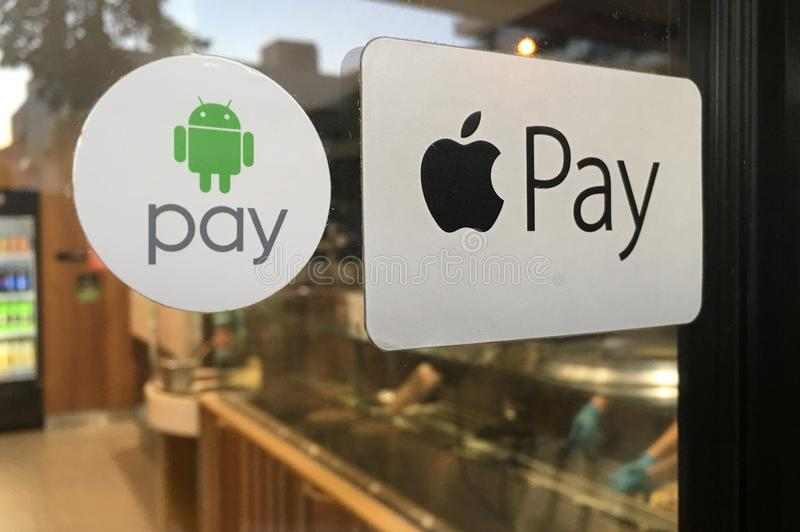 Apple and Android Pay Stickers on a Door. To a restaurant. It is a mobile payment and digital wallet service by Apple Inc and Google stock images