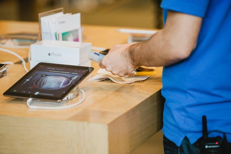 Apple anställd som räknar lanseringen för pengarduirngiPhone arkivbild