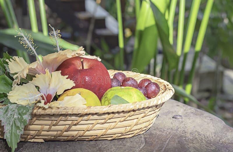 Apple, arancia ed uva nei canestri di bambù del tessuto con gli alberi confusi del fondo floreale delle decorazioni fotografie stock