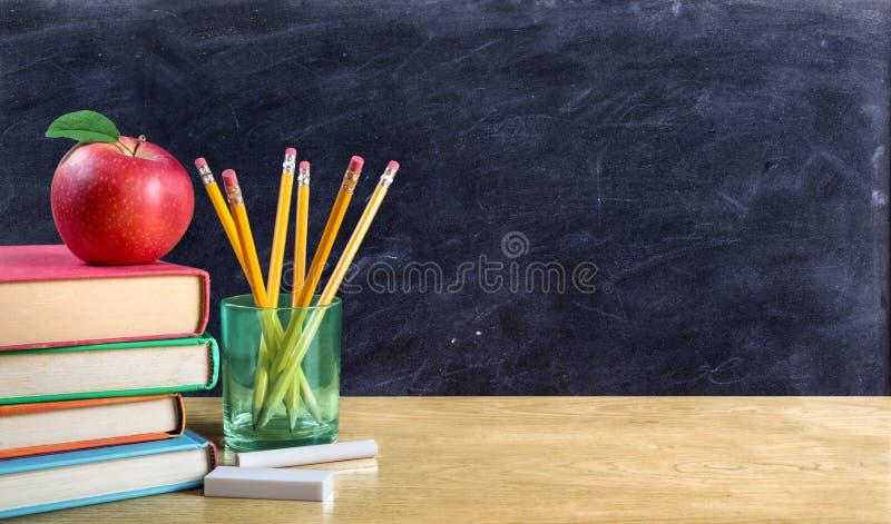 Apple auf Büchern mit Bleistiften und leerer Tafel stockbild