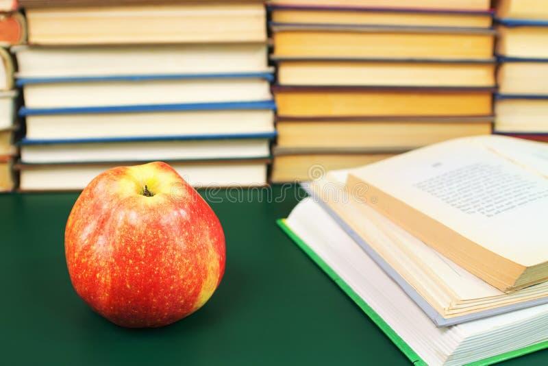 Apple auf der grünen Tabelle und den geöffneten Büchern lizenzfreies stockfoto