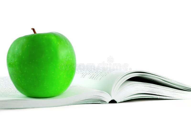 Apple auf einem Buch stockfotografie