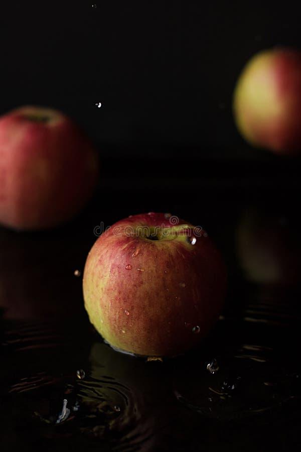 Apple avec de l'eau se laisse tomber sur un fond noir Clé foncée photos stock