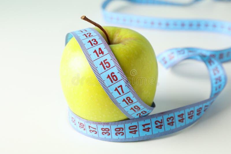 Apple avec la bande de mesure sur le fond blanc image stock
