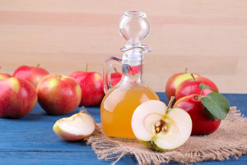 Apple-azijn naast rode appelen op een blauwe lijst aangaande een natuurlijke houten achtergrond stock foto
