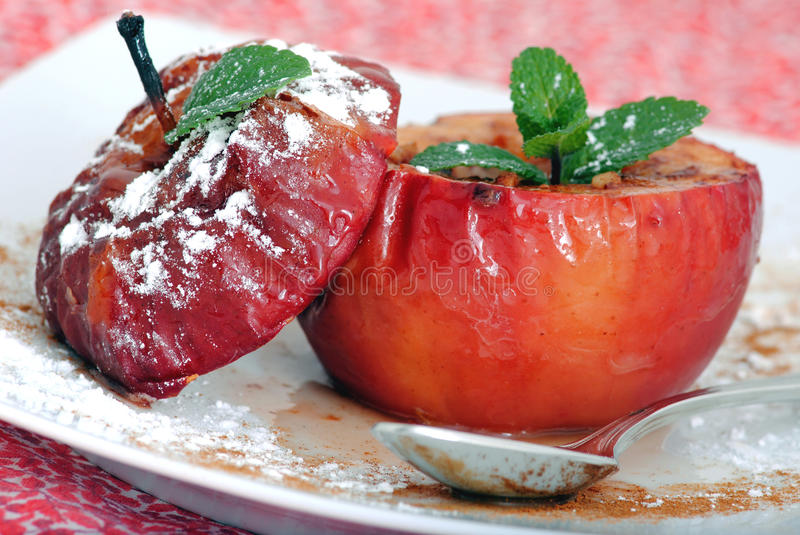 Apple baked dessert. Baked apples dessert with cinnamon, honey, raisins with cutlery decorated with icing sugar and mint leaf on red background royalty free stock photo