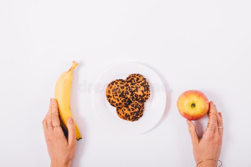 Apple, banan och en platta av kakor i kvinnliga händer arkivfoton
