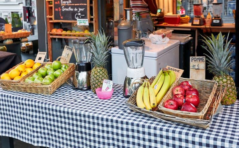 Apple, Banane und Orange in den Körben und eine Mischmaschine auf dem Zähler einer Fruchtsaftstange im Freien stockbilder