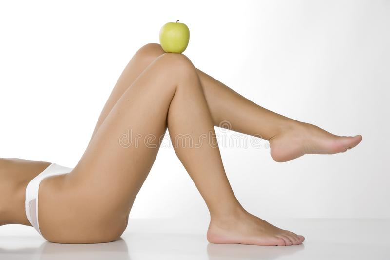 Apple on the belly of beautiful woman royalty free stock images