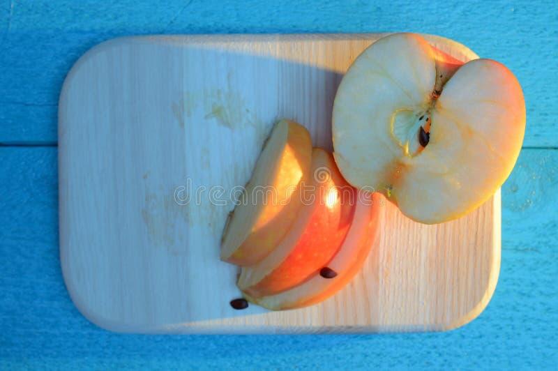 Apple-besnoeiing in plakken op een houten raad op turkooise lijst met een lange blauwe schaduw stock foto