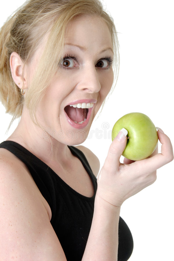 Apple bites. Woman with mouth open about to take a bite of an apple on white