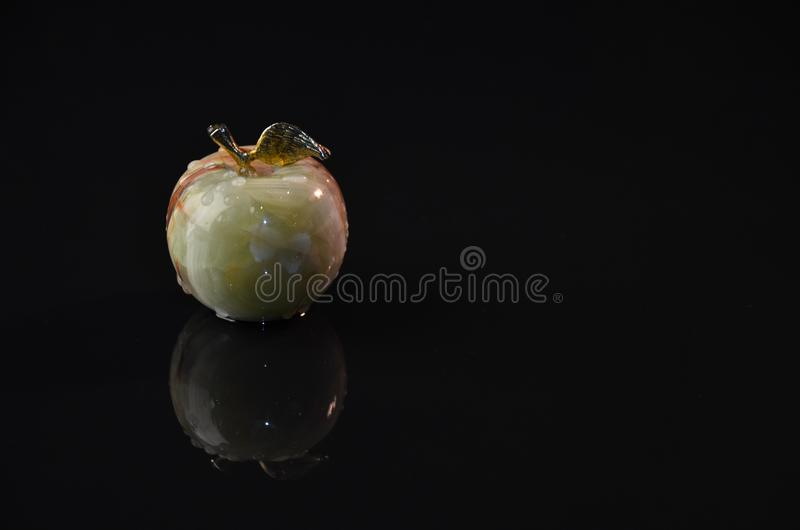 Apple on black background by candlelight stock photography