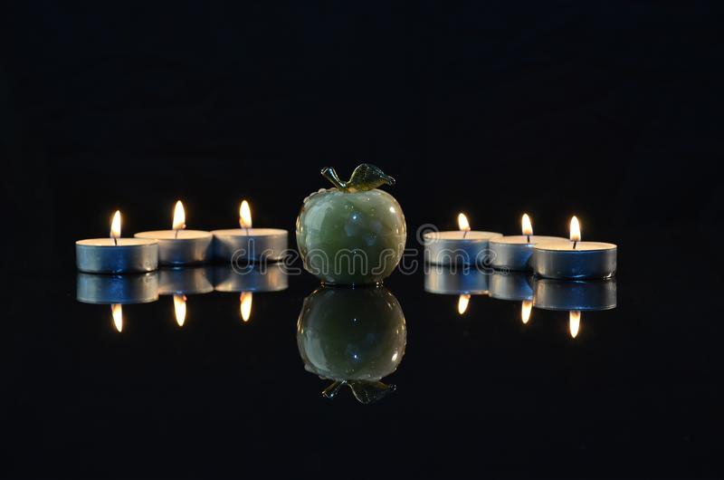 Apple on black background by candlelight stock image