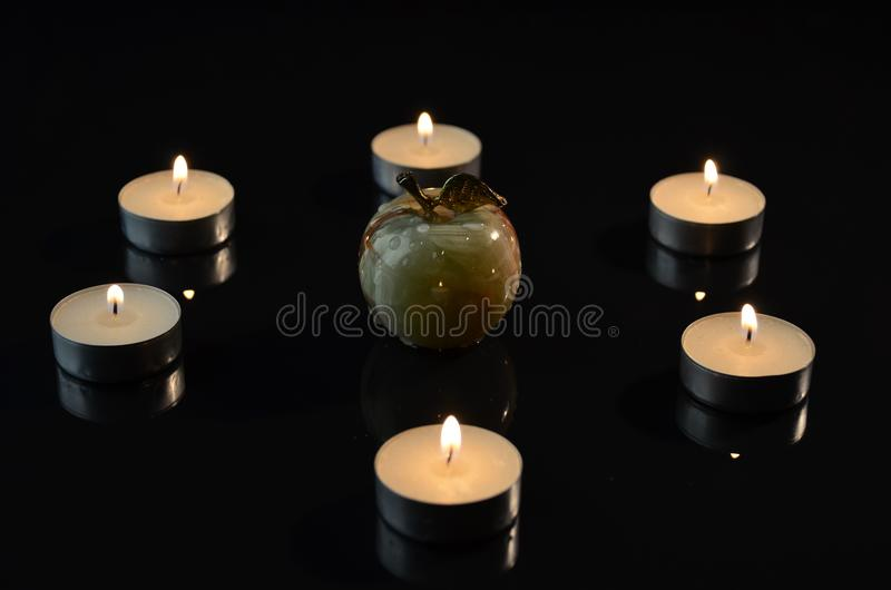 Apple on black background by candlelight royalty free stock photo