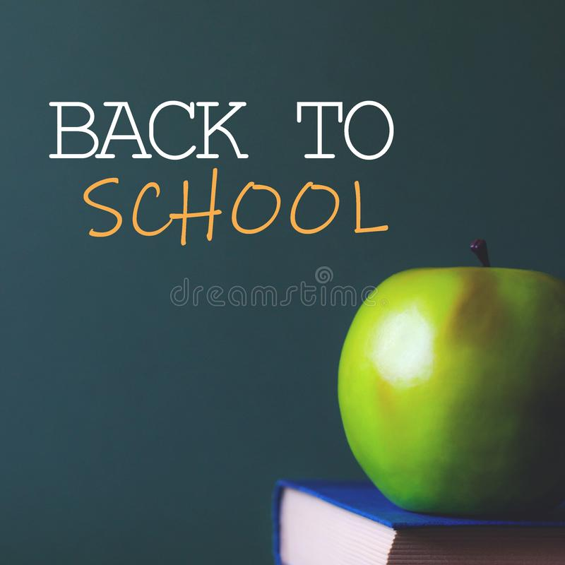 An apple on the book and next to the inscription back to school royalty free stock photos