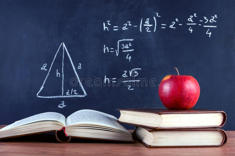 Apple on books and blackboard with Pythagorean theorem stock photography