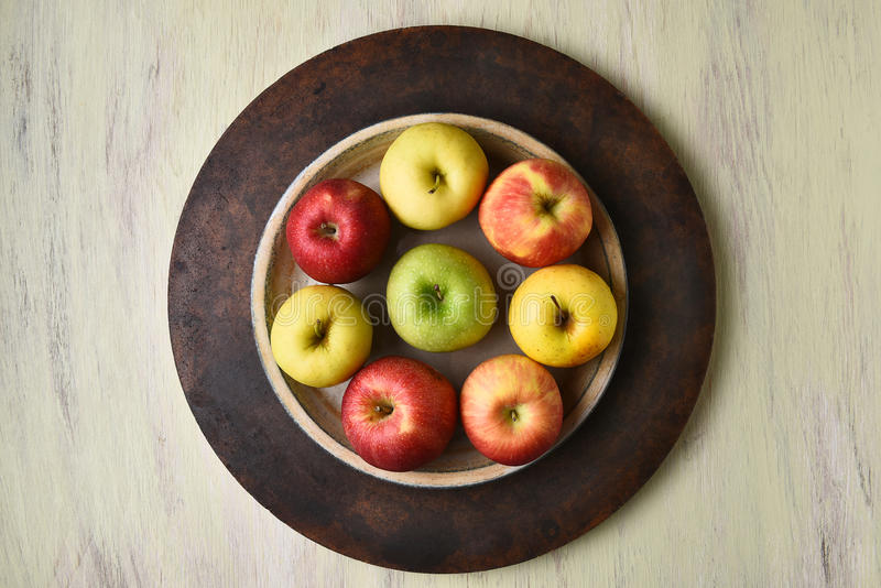 Apple Bowl Still Life. High angle view of a bowl of assorted apples on a rustic table stock photo