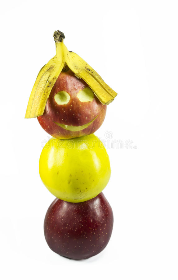 Apple boy. Three overlapped apples the top one with carved eyes and mouth and banana peel as hair , resembling a smiling human face, isolated on white stock images