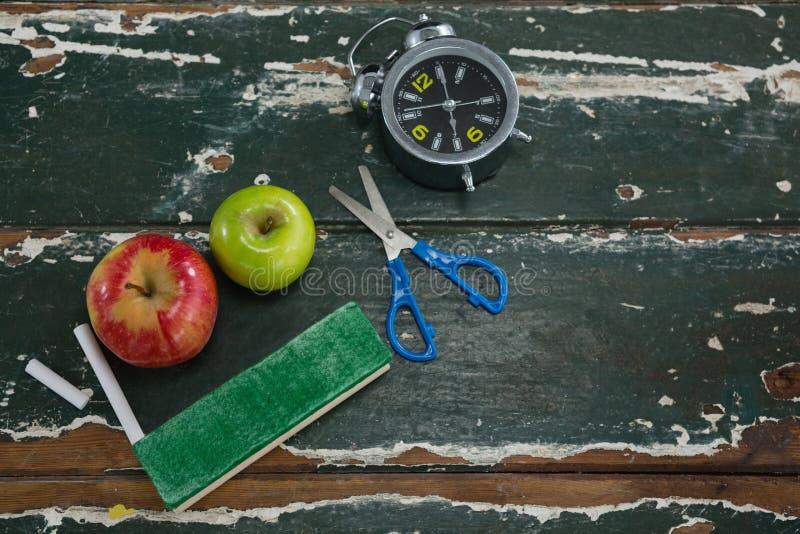 Apple, budzik, duster, nożyce i kreda na drewnianym stole, fotografia royalty free
