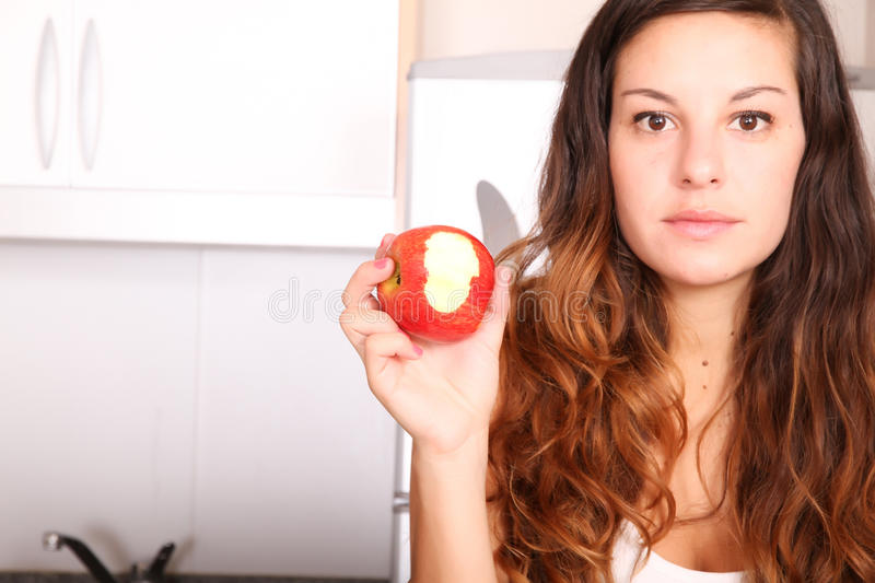 Apple byte. A young adult woman with fruits and wine in the kitchen royalty free stock photos