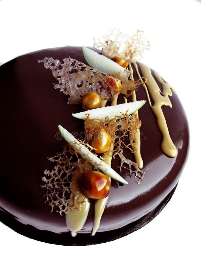 Apple and caramel chocolate cake with caramelized hazelnuts, crepe lace and mirror glaze royalty free stock photography