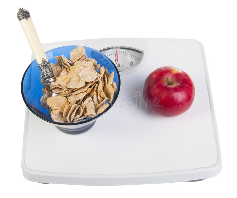 Apple and cereal on the scales. Red apple and bowl with cereal on the white floor scales isolated on the white background stock images