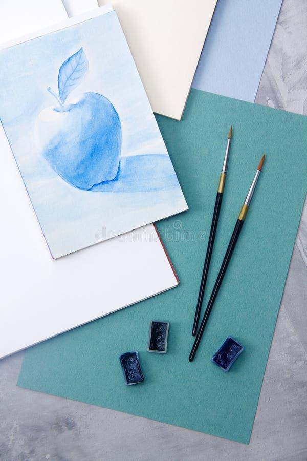 Apple che assorbe i colori blu, carta dell'acquamarina, spazzole, waterco fotografie stock