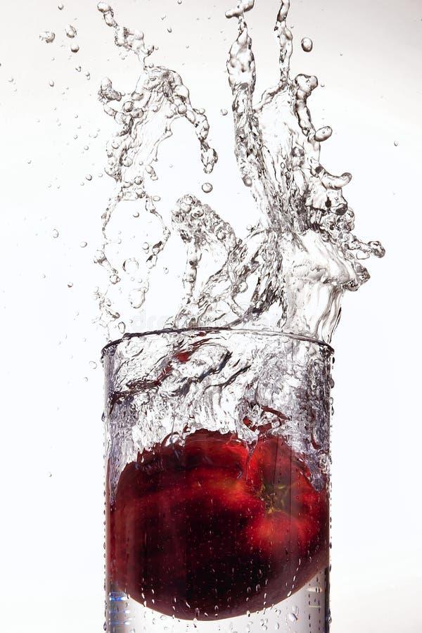 Apple che spruzza in vetro di acqua fotografie stock