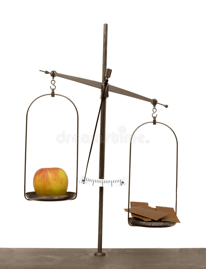 Apple and chocolate on scales. Apple and chocolate on old antique balancing scales royalty free stock photography
