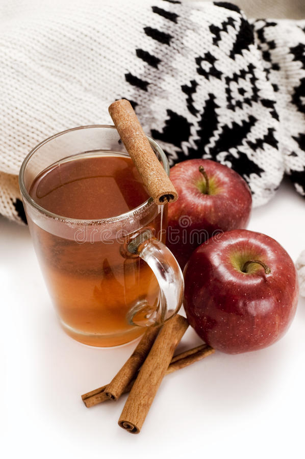 Apple cider. Cup od apple cider and rolls of cinnamon royalty free stock photos