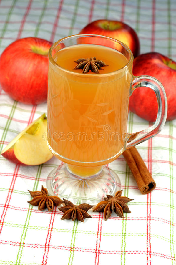Apple Cider. Fresh apple cider with cinnamon, anise seed, and cloves, on red, white and green tablecloth royalty free stock images