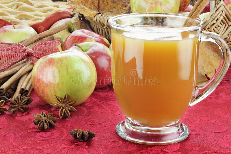 Apple Cider and Apples. Hot apple cider with cinnamon bark, anise stars and fresh apples. Shallow depth of field with selective focus on cider stock image