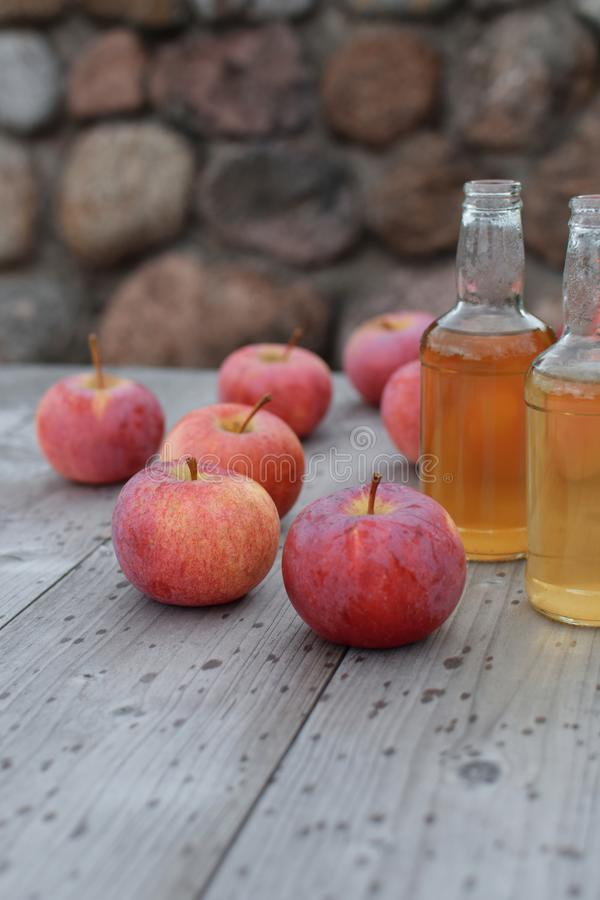 Apple cider and apples. Apple cider beverage in two glass bottles and red ripe fresh apples on grey natural wooden table background with rain drops with copy royalty free stock images