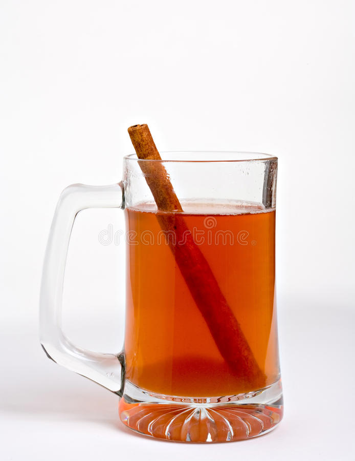 Apple cider with cinnamon stick. Hot apple cider in clear glass with cinnamon stick stock photography