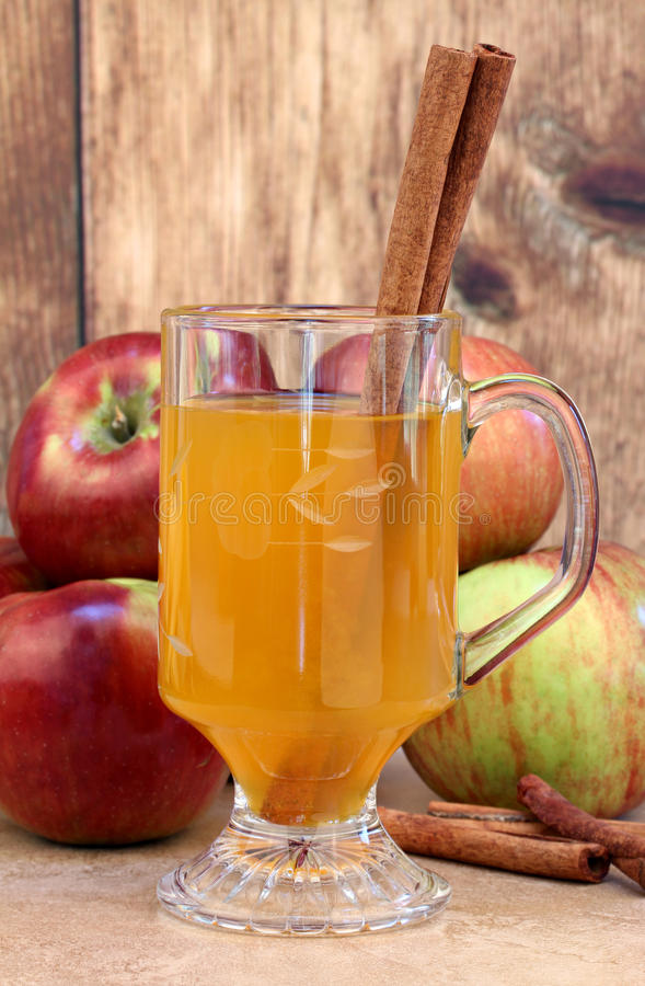 Apple cider with cinnamon sticks and apples. Close up glass of apple cider with cinnamon sticks. Apples in the background stock image