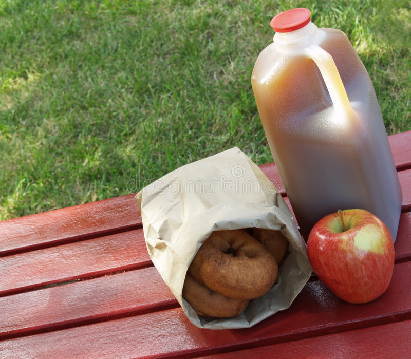 Apple cider and donuts. Fall - an apple, a jug of apple cider and a bag of donuts on a red picnic table royalty free stock photos