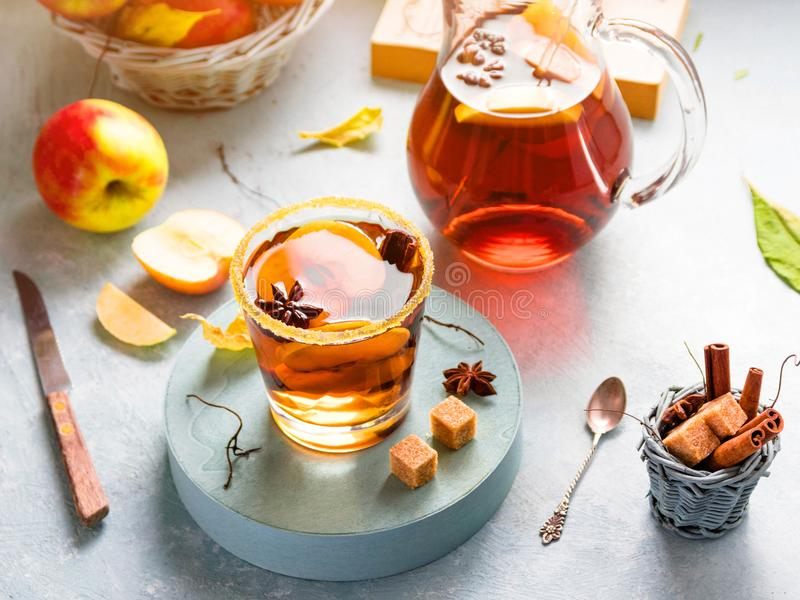 Apple cider drink, hot cocktail with cinnamon sticks and apple slices. Tea with spices. Autumn sunny cozy morning mood. Romantic atmosphere stock image