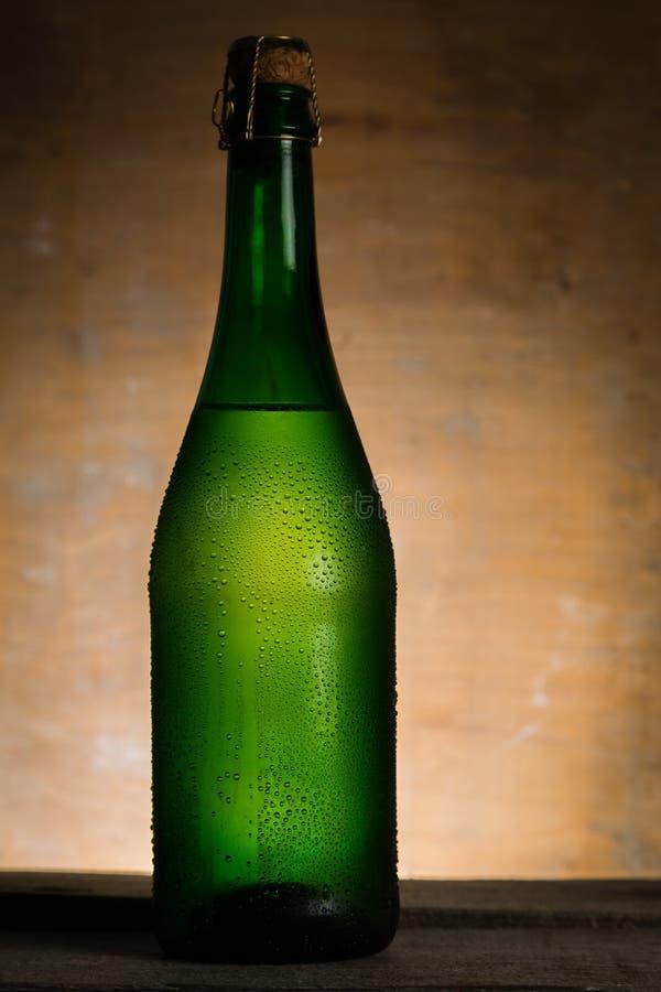 Apple-cider in glasfles met waterdalingen stock fotografie