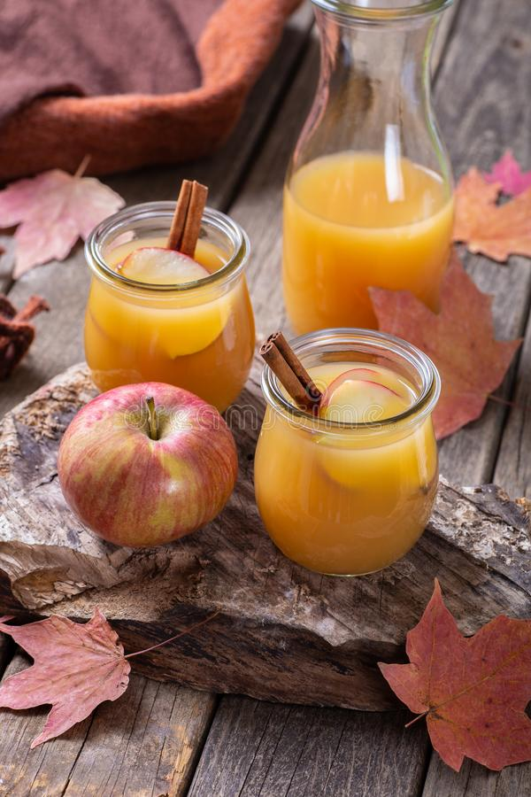 Apple Cider In Glass Jars. Two glass jars of apple cider with cinnamon sticks and apple slices on a rustic wooden surface with autumn leaves royalty free stock photos