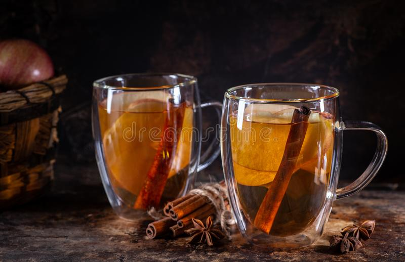 Apple Cider in Glass Mugs. Two glass mugs of apple cider with cinnamon sticks and sliced apples on a rustic surface and dark background stock photo