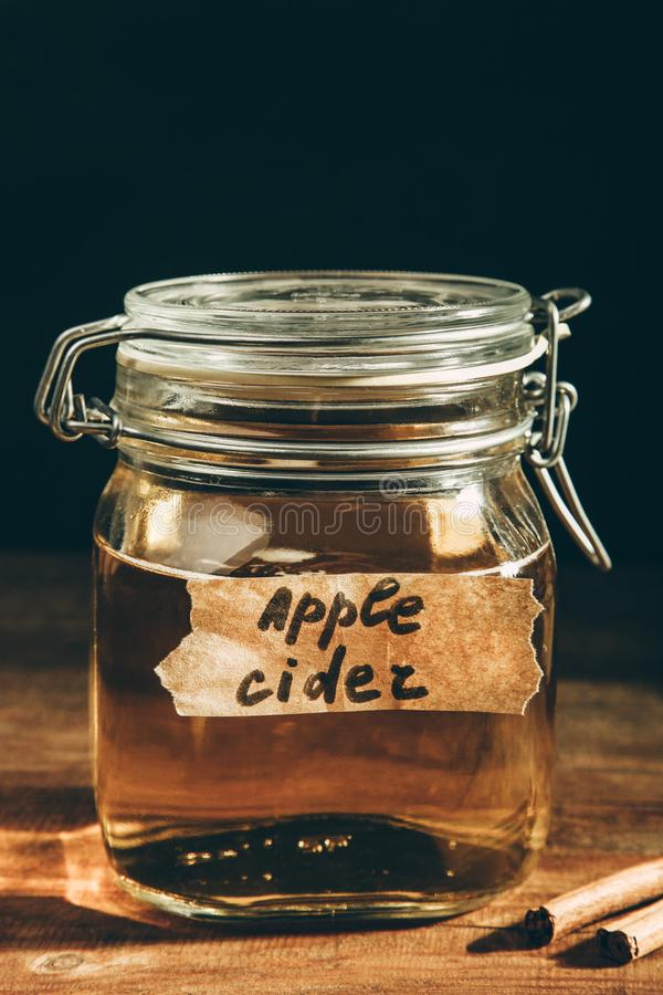 Apple cider in jar. On a wooden table on black background. Concept alcoholic beverage royalty free stock image