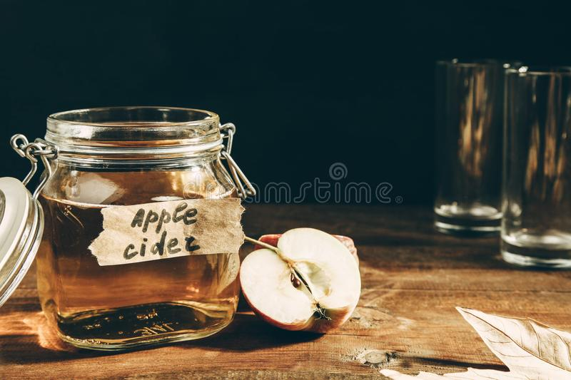 Apple cider in jar. On a wooden table on black background. Concept alcoholic beverage stock photography