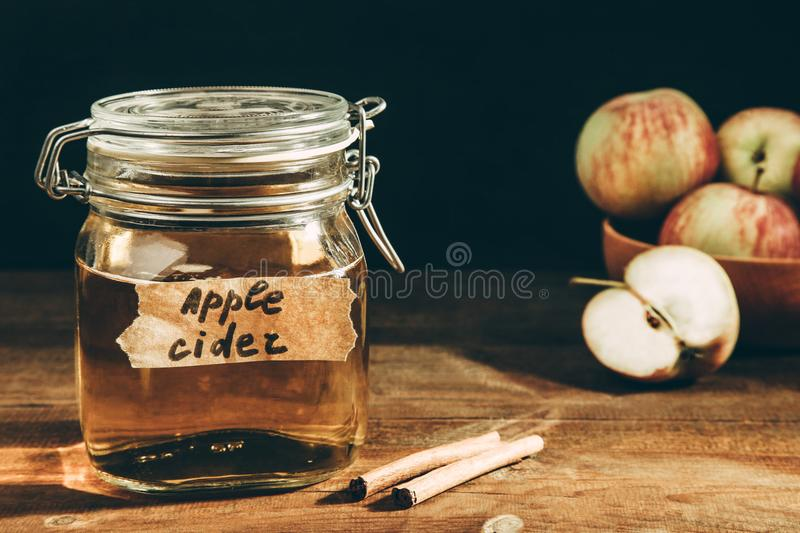 Apple cider in jar. On a wooden table on black background. Concept alcoholic beverage royalty free stock photo