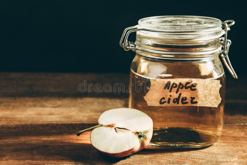 Apple cider in jar. On a wooden table on black background. Concept alcoholic beverage royalty free stock photography
