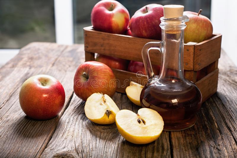 Apple cider vinegar and apples on a wooden table. Fruit-organic-apples-vegetarian stock photo