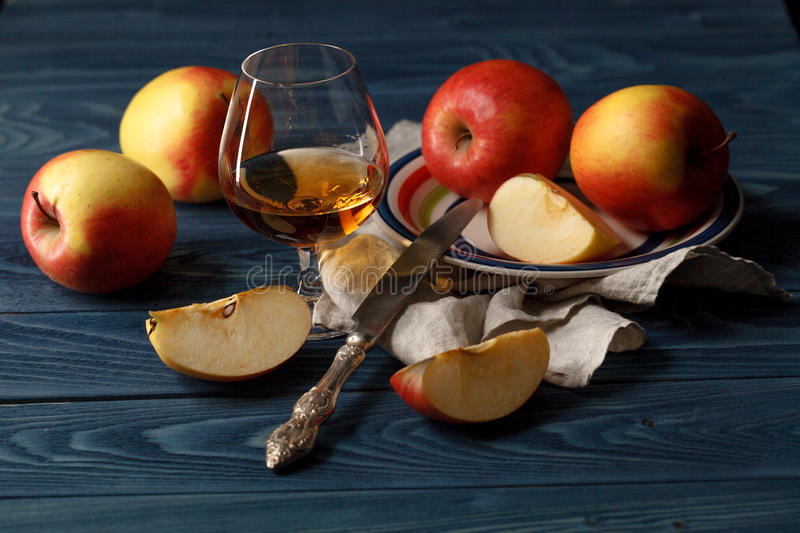Apple cider in wine glass with cinnamon sticks and fresh apples. On wooden background royalty free stock photo