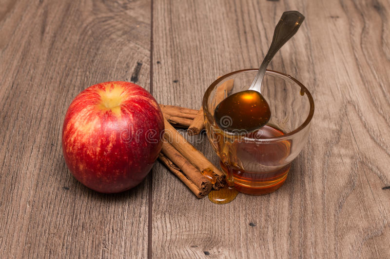 Apple, cinnamon sticks, and a glass with honey royalty free stock image