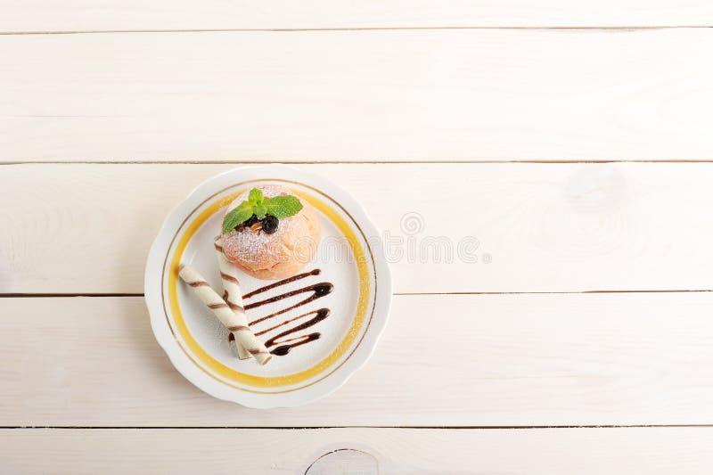 Apple cocido con la oblea rueda en una placa con el chocolate y el powde foto de archivo libre de regalías