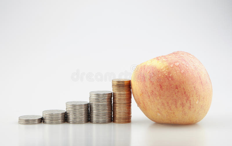 Apple and coins. Color photo of an apple and a stack of coins stock photos